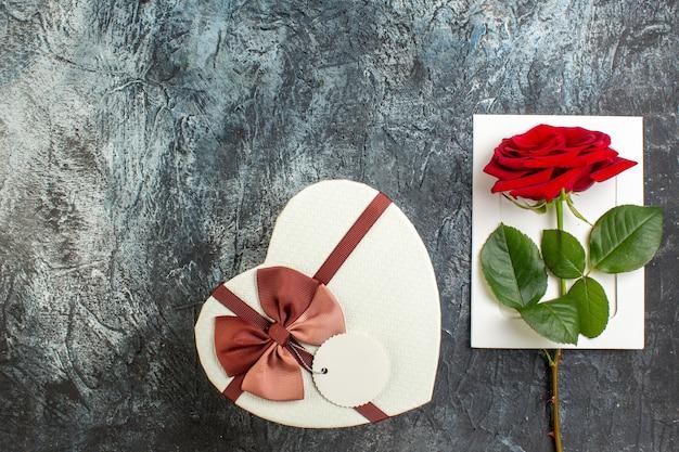 Вид сверху красная роза с подарком на день святого валентина на светло-сером фоне сердце чувство любовь праздник страсть брак пара
