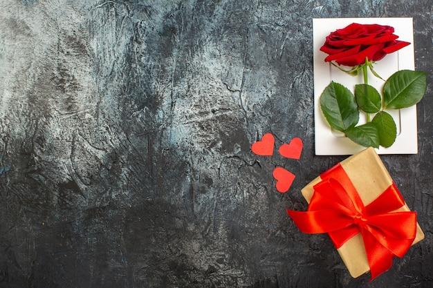 Вид сверху красная роза с подарком на день святого валентина на светло-сером фоне пара брак страсть праздник сердце чувство любовь свободное пространство