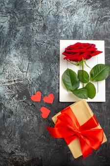 Вид сверху красная роза с подарком на день святого валентина на светло-сером фоне пара брак страсть праздник сердце чувство любви
