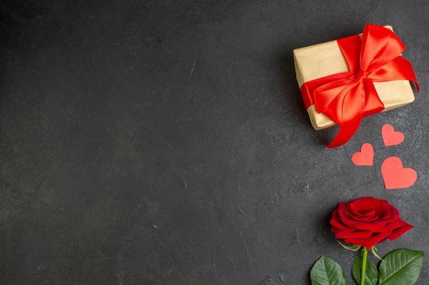 Вид сверху красная роза с подарком, перевязанная красным бантом на темном фоне любовь пара страсть день святого валентина цвет настоящее сердце