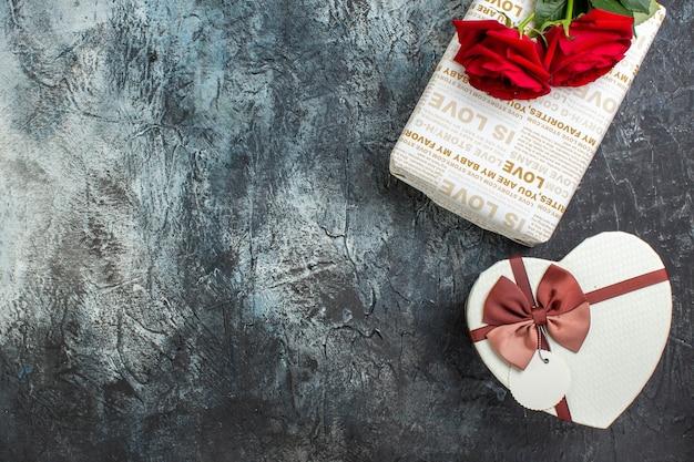 Vista dall'alto di rose rosse e bellissime scatole regalo su sfondo scuro ghiacciato con spazio libero