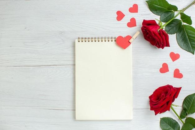 愛の情熱の恋人の心のカップルの休日を感じて白い背景の上のバレンタインデーのトップビュー赤いバラ