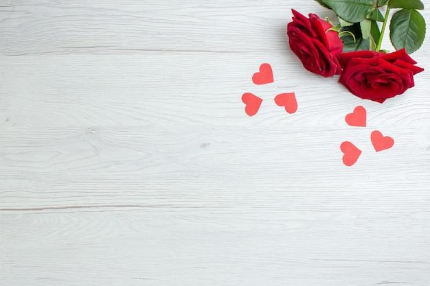 Вид сверху красные розы на белом фоне любовь праздник страсть любовник пара брак сердце чувство записка