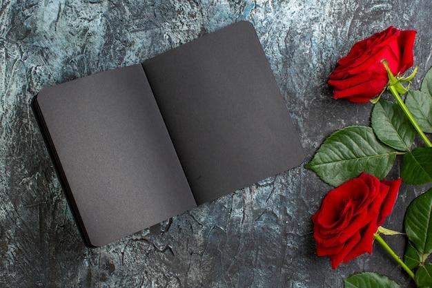 Вид сверху красные розы с темной тетрадкой на день святого валентина на светло-сером фоне сердце чувство любовь пара праздник страсть брак