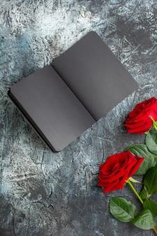 밝은 회색 배경에 발렌타인 데이를 위한 어두운 카피북이 있는 상위 뷰 빨간 장미 심장 느낌 사랑 휴가 열정 결혼 커플