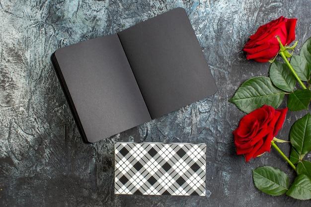 Вид сверху красные розы с темной тетрадкой на день святого валентина на светло-сером фоне сердце чувство любовь любовник пара праздник страсть брак