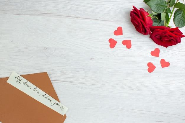 Вид сверху красные розы с запиской на белом фоне праздник страсть любовник пара брак сердце любовь чувство записка