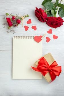 Вид сверху красные розы с блокнотом и подарок на белом фоне любовь праздник страсть любовник пара брак сердце чувство примечание