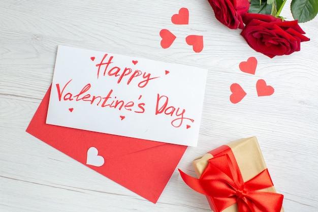 Вид сверху красные розы с блокнотом и подарок на белом фоне любовь праздник страсть любовник пара брак сердце чувство