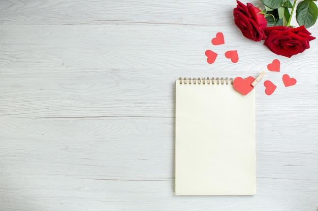 Вид сверху красные розы с блокнотом на белом фоне любовь праздник страсть любовник пара брак сердце чувство записка