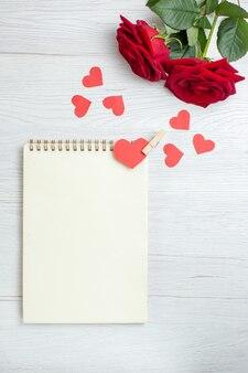 Вид сверху красные розы с блокнотом на белом фоне любовь праздник страсть любовник пара брак сердце чувство ноты
