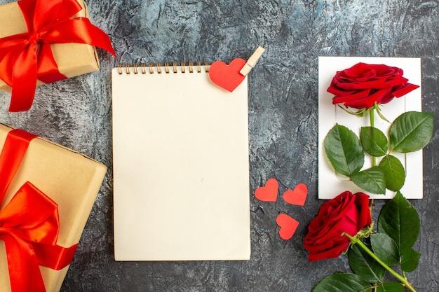 Вид сверху красные розы с подарком на день святого валентина на светло-сером фоне пара брак любовь праздник сердце чувство