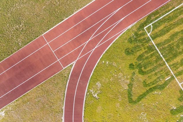 Top view of red running tracks and green grass lawn. infrastructure for sports activities.