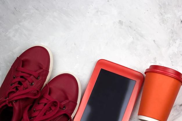 Вид сверху красные кроссовки, планшет, кофейная чашка
