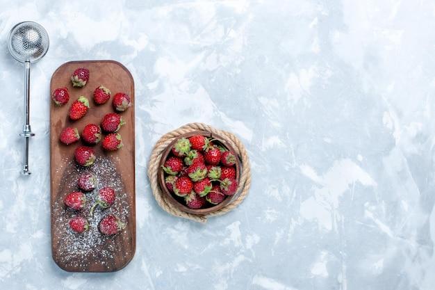 明るい白い机の上に赤いイチゴの新鮮でまろやかな果物の上面図