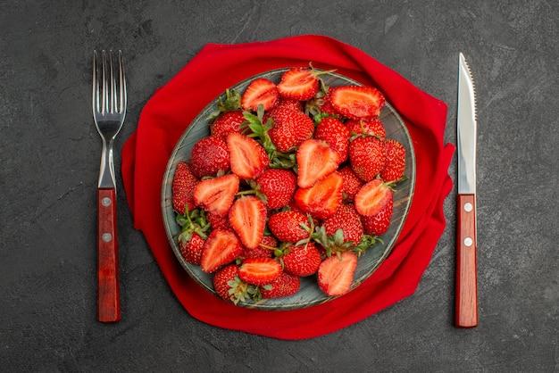 Вид сверху красной клубники внутри тарелки на темном фоне