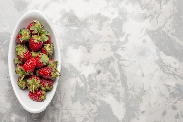 Vista dall'alto fragole rosse all'interno della piastra su sfondo bianco frutti di bosco pianta selvatica albero mellow