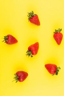 Вид сверху красная клубника спелые сочные изолированные на желтом фоне