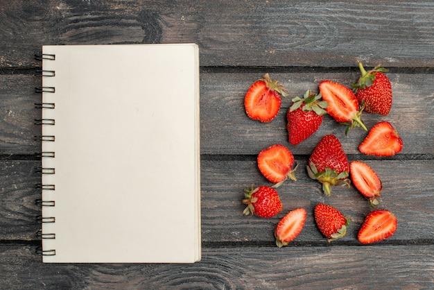 暗い木製の素朴な机の上にスライスされた赤いイチゴと果物全体の上面図