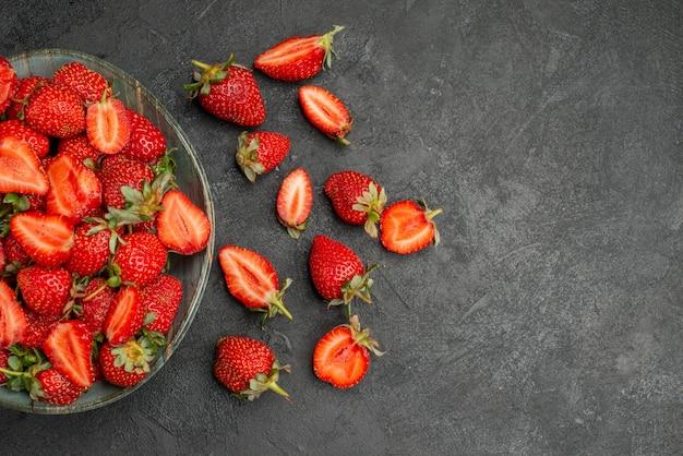 灰色の背景にスライスされた赤いイチゴと果物全体の上面図