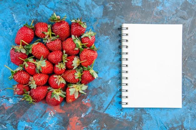 青い背景の上のメモ帳とトップビューの赤いイチゴ
