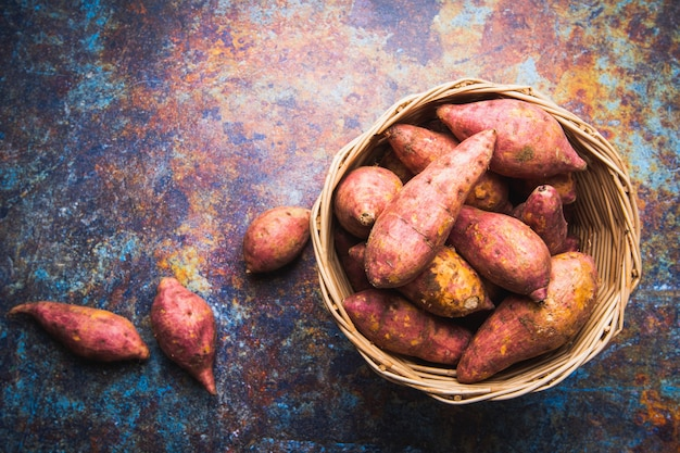 Top view red sweet potatoes in basket, flat lay raw food display on grunge metal background with copy space