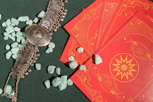 Top view red tarot cards next to vintage necklace