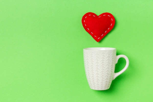Top view of red textile heart splashing out of a cup