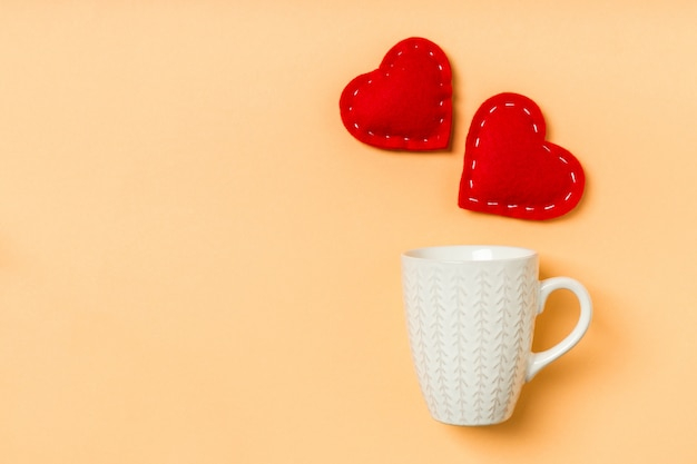 Top view of red textile hearts splashing out of a cup