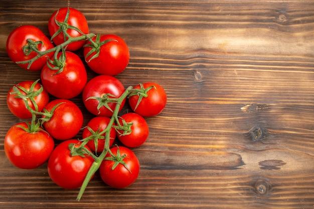 Вид сверху красные помидоры, спелые овощи на коричневом деревянном столе