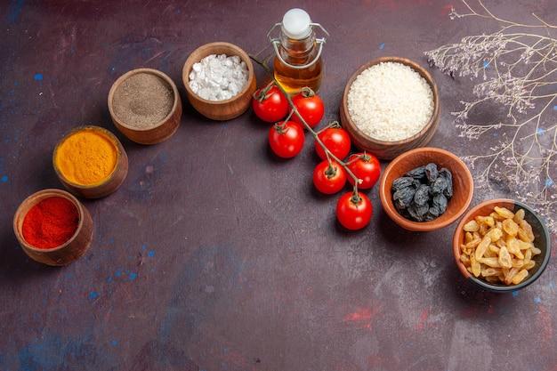 暗い背景にレーズンと調味料を添えたトップビューの赤いトマトレーズン野菜サラダの健康