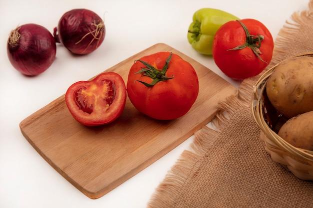 Vista dall'alto di pomodori rossi su una tavola di cucina in legno con patate fresche su un secchio su un panno di sacco con cipolle rosse e pepe verde isolato su un muro bianco