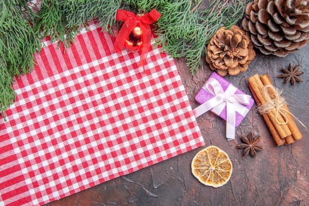 Vista dall'alto tovaglia a scacchi bianca e rossa rami di pino pigne regalo di natale cannella albero di natale giocattolo a sfera su superficie rosso scuro