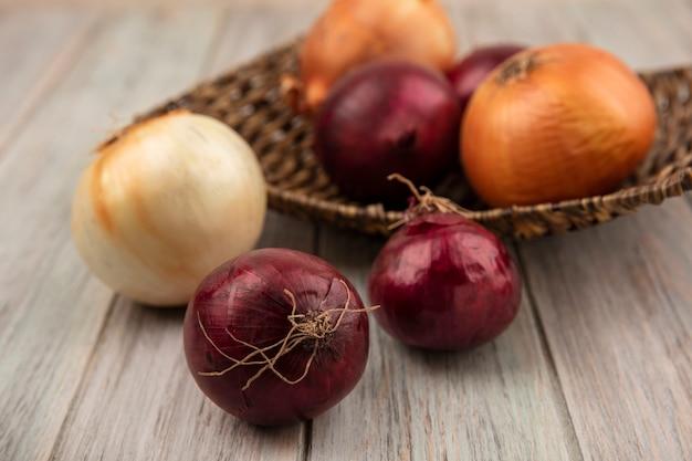 Vista dall'alto di cipolle rosse e bianche su un vassoio di vimini su una superficie di legno grigia