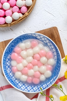 Top view of red and white tangyuan (tang yuan, glutinous rice dumpling balls) in blue bowl on white background for winter solstice festival food.