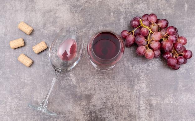 メガネとブドウの水平方向の暗い石の上から見る赤ワイン