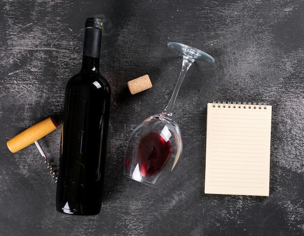 Vino rosso di vista superiore con lo spazio della copia in taccuino sull'orizzontale di pietra nero
