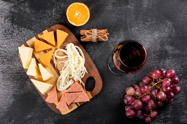 Top view of red wine with grape, orange and cheese on wooden cutting board on dark surface horizontal