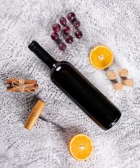 Vista superiore di vino rosso con uva, arancia e cannella sull'orizzontale di pietra bianco