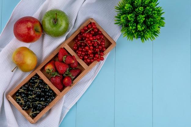Вид сверху красный с черной смородиной с клубникой и яблоками на голубом фоне
