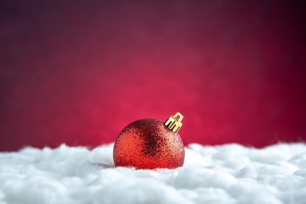 Vista dall'alto palla rossa dell'albero di natale sul tavolo rosso isolato