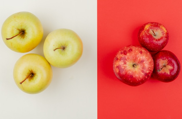 Top view of red and yellow apples on ivory and red background
