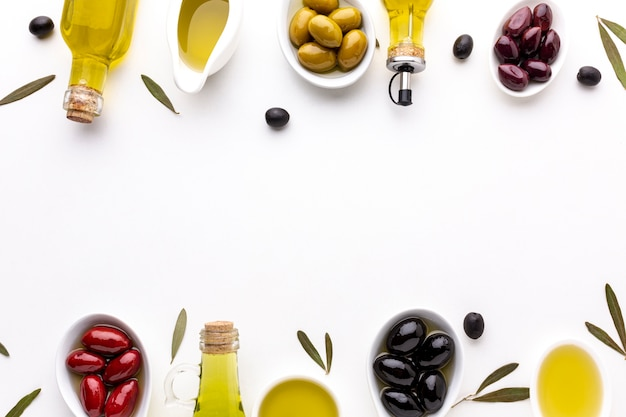 Top view red yellow black olives in spoons with oil bottles and copy space