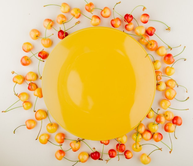 Top view of red and yellow cherries with empty yellow plate on center on white surface