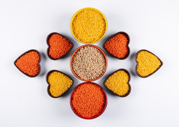 Top view red, yellow and green lentils in different colored and heart shaped blows