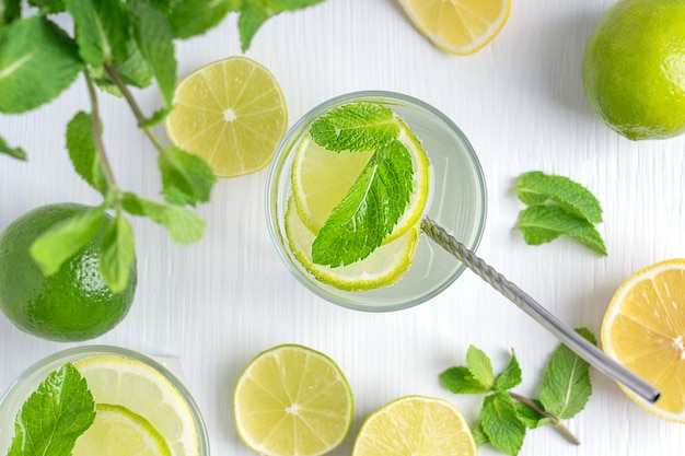Top view on refreshing lemonade of lemon and lime slices sparkling water and mint on white table