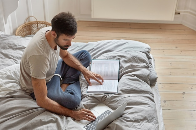 Top view of relaxed bearded guy poses at cozy bed in lotus pose, ponders on readed material, checks information from book in laptop computer, studies laws, works in bedroom. domestic atmosphere