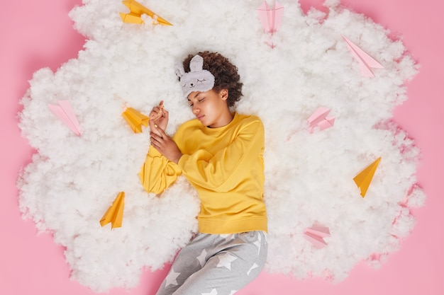 Top view of relaxed dark skinned young woman dressed in pajama sleepmask poses on fluffy white cloud