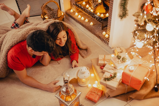 Top view of relaxing couple covered by a soft and cozy blanket at home reading a book together under the fireplace with candles, presents and decorated tree.
