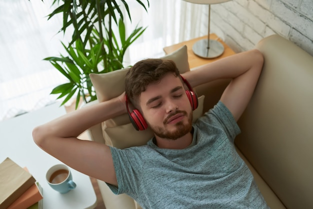 Top view of relaxing student in headphones enjoying his lounge playlist